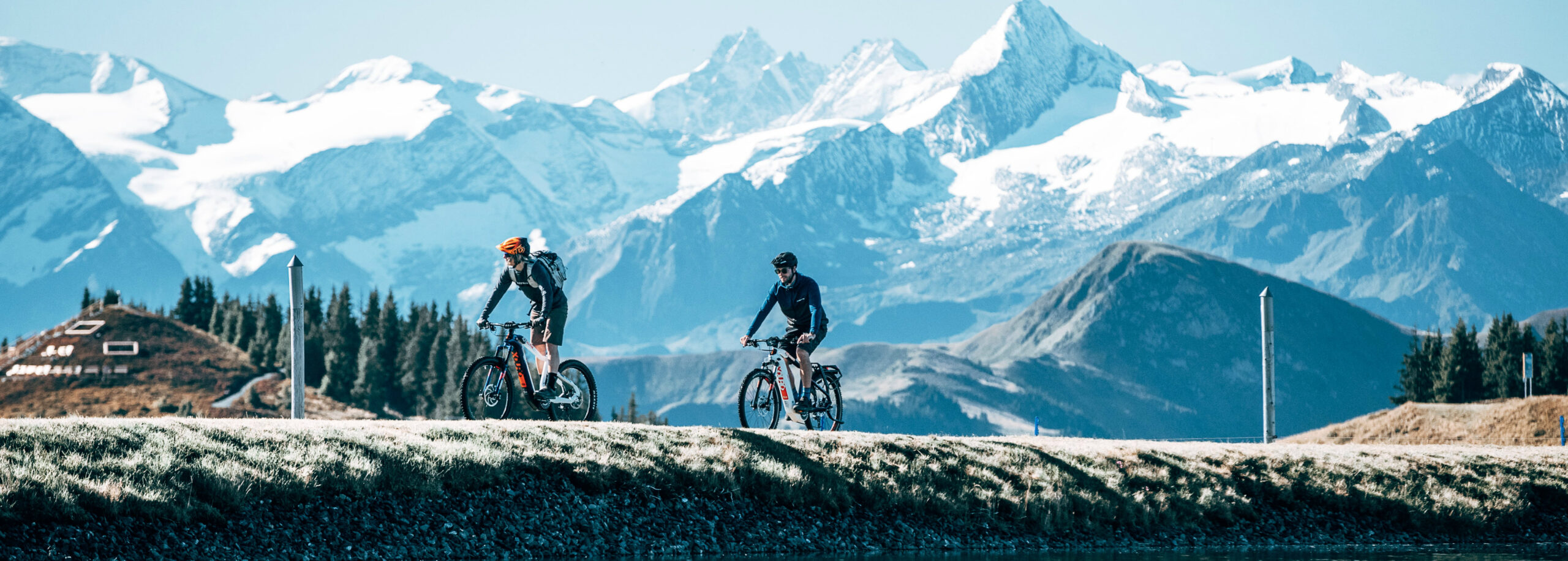 This is the image of two cyclists riding e-bikes with mountains in the background